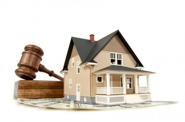 Home, money and gavel real estate concept; isolated on white with shallow depth of field