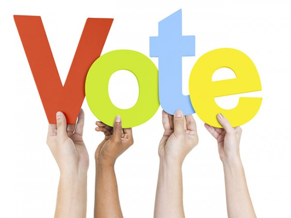 Group of People's Hands Holding Word Vote